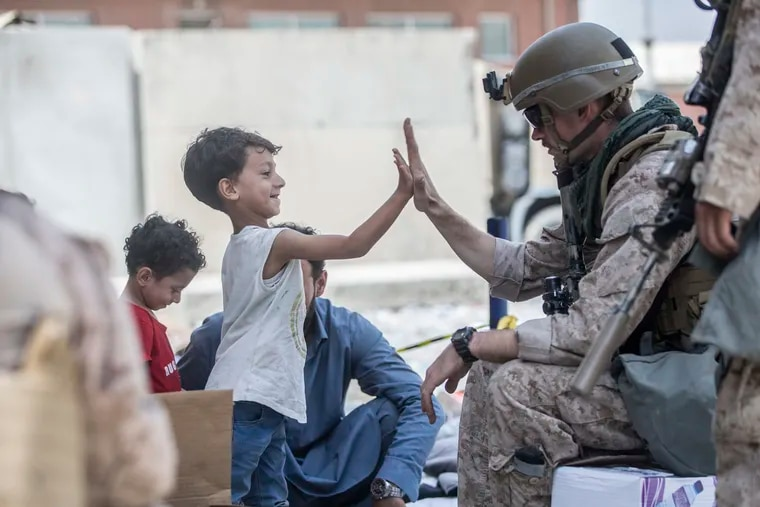 A Marine gives a high five Sunday to a child during an evacuation at Hamid Karzai International Airport in Kabul.