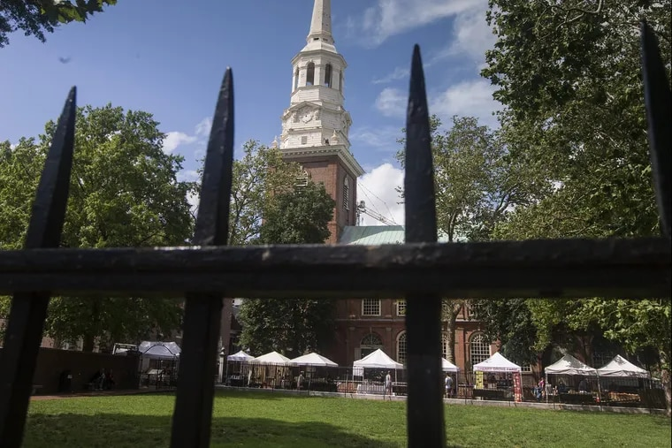 The fenced in lawn at Second and Market could be the answer to a park in Old City. The National Park Service owns the space. Christ Church looms above the park area on Aug. 1, 2018. A farmer's market is in the background. CHARLES FOX / Staff Photographer