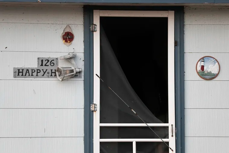 A light fixture hangs in front of a happy home that was damaged on Arnold Boulevard. in the High Bar Harbor section of Long Beach Twp. on N.J.'s Long Beach Island on July 30, 2021. Violent storms, that included tornados, left their marks in both Pa. and N.J. the previous evening.