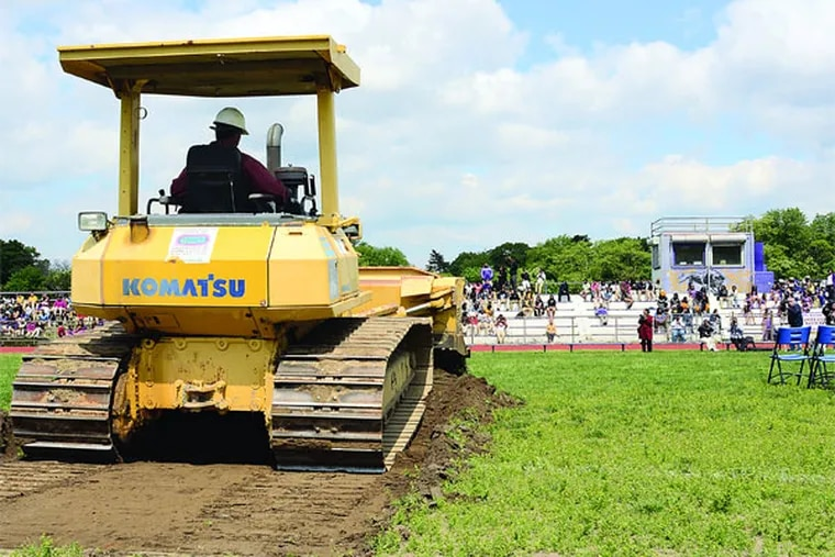 A bulldozer moves some earth during the official ground-breaking ceremony May 13, 2013, for the $1.5 million renovations to the Camden High School football field. The field has been in desperate need of renovations for while- no lights, scrapy field with holes, bleachers are in terrible condition. The Eagles donated a portion of the costs. ( TOM GRALISH / Staff Photographer )