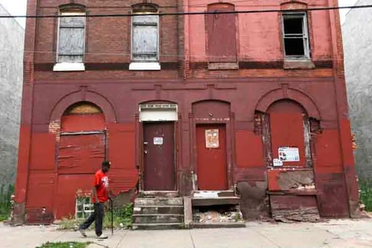 "A man walks through a blighted neighborhood, Thursday, July 11, 2013, in Philadelphia. Mayor Michael Nutter announced Thursday an anti-poverty plan called ""Shared Prosperity Philadelphia."" (AP Photo/Matt Rourke)"