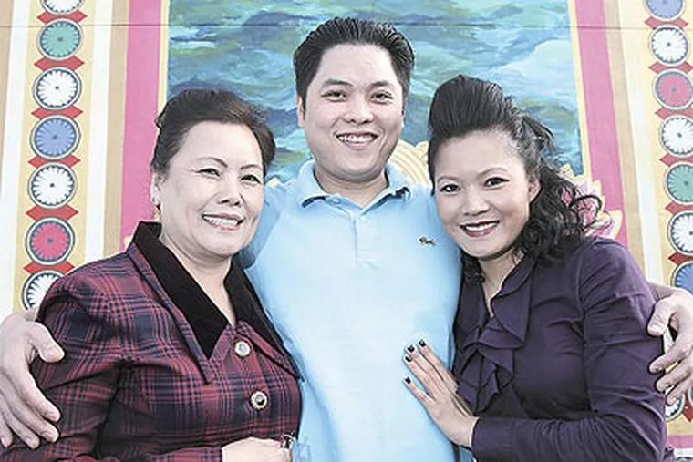 At the exhibit on Vietnamese refugees at the Asian Arts Initiative are (from left) Hien Cao with son Michael Quang Vo and daughter Kim Vo. (Steven M. Falk / Staff Photographer)