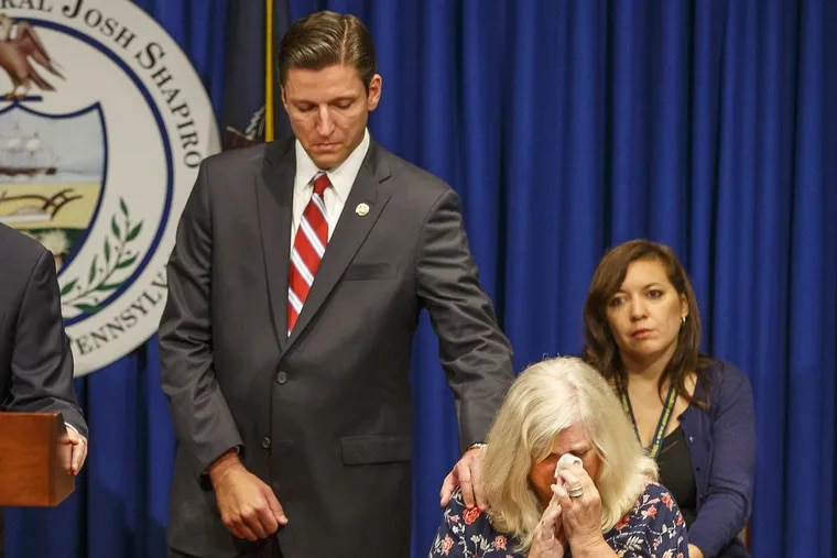 Daniel J. Dye, senior deputy attorney general, reaches over and comforts Judy Deavena, mother of Joey Behe, a victim of sexual abuse by a Catholic priest.