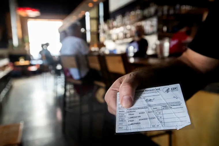 A customer at Martha shows his vaccination card on July 31, 2021.