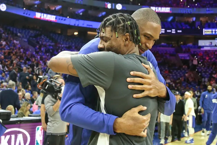 The Sixers' Al Horford (rear) gets a hug from former Celtics teammate Marcus Smart before the season opener at the Wells Fargo Center.
