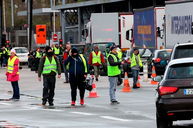 """Demonstrators wearing yellow vests on the blocked highway near the French border with Spain, during a protest Saturday, Dec. 15, 2018 in Biriatou, southwestern France. Police have deployed in large numbers Saturday for the fifth straight weekend of demonstrations by the """"yellow vest"""" protesters, with authorities repeating calls for calm after protests on previous weekends turned violent. (AP Photo/Bob Edme)"""