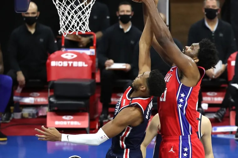 Joel Embiid, right, of the SIxers grabs a rebound over Troy Brown Jr. of the Wizards during the first half of Wednesday's win.