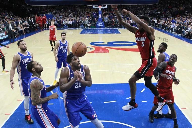 Derrick Jones, of the Heat dunks over Joel Embiid during the 2nd half at the Wells Fargo Center on Dec. 18, 2019.