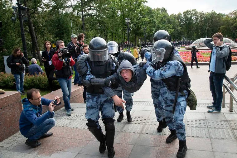 Police officers detain a protestor, during an unsanctioned rally in the center of Moscow, Russia, Saturday, Aug. 3, 2019. Moscow police detained more than 300 people Saturday who are protesting the exclusion of some independent and opposition candidates from the city council ballot, a monitoring group said.