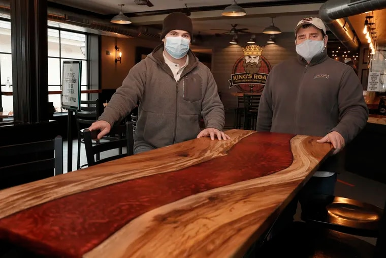Woodworker Jeff Braddock (left) and Kings Road Brewing Company owner Bob Hochgertel admire a table made from a buttonwood tree that stood in downtown Haddonfield, NJ for 250 years. Pieces of the tree have been salvaged and made available for use by local artisans as part of a grassroots movement to upcycle wood from fallen or removed trees. Braddock, of Moorestown, designed and handcrafted the table for the brewing company.