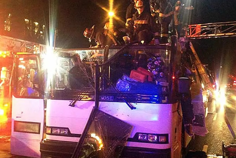 In this photo released by the Boston Fire Department via Twitter, firemen work to remove injured passengers from a bus that hit an bridge as it traveled along Soldiers Field Road in the Allston neighborhood of Boston Saturday night, Feb. 2, 2013. Officials said the bus carrying 42 people was traveling from Harvard University home to Pennsylvania when it struck the overpass. (Boston Fire Department/AP)