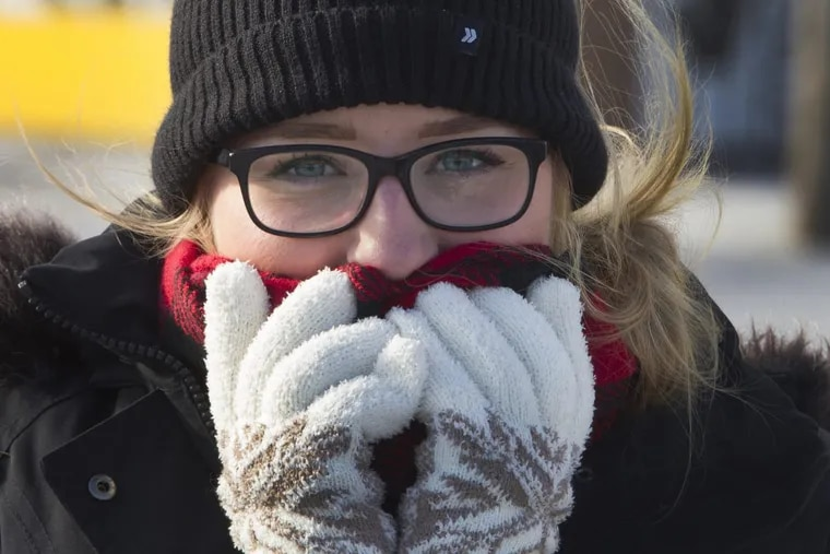 Morgan Hamilton from Woodstown, New Jersey, covers her face from the cold wind during a blistery cold morning in Philadelphia, Pa. Sunday, Dec. 31, 2017.