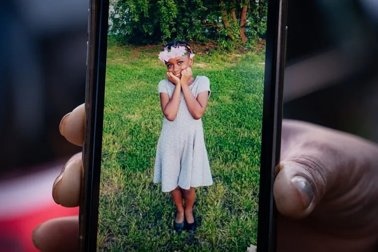 A family member holds up a cell phone with a photo of Fanta Bility.