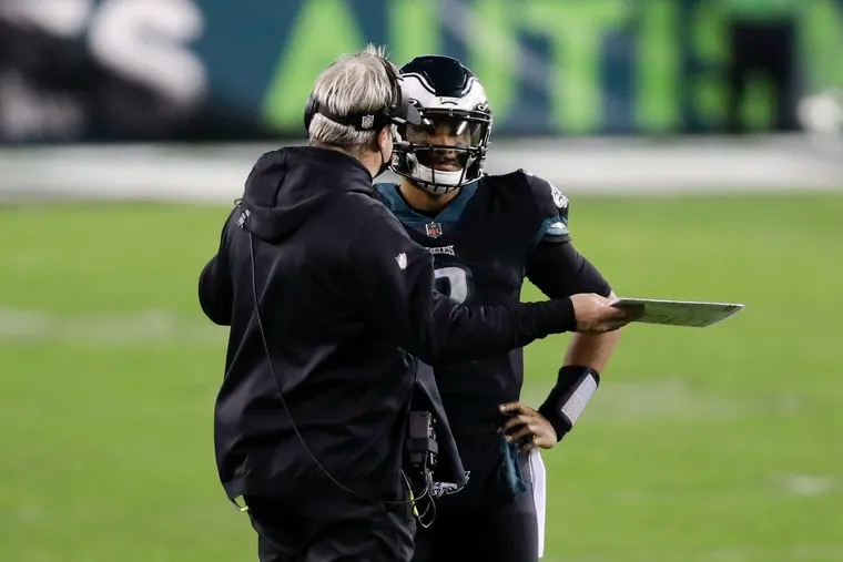 Eagles head coach Doug Pederson talks to quarterback Jalen Hurts during the offense's last possession against the Saints in Sunday's 24-21 win.
