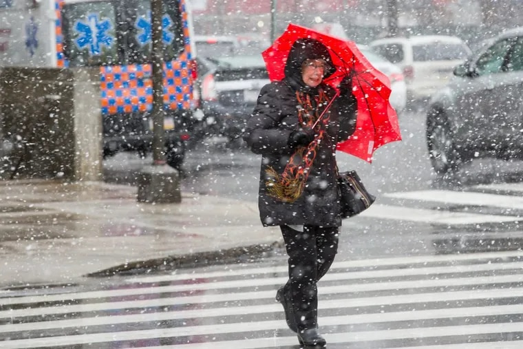 A pedestrian uses an umbrella to brace against the inclement weather at 15th and JFK Blvd., in Center City Philadelphia, Friday, March 2, 2018.