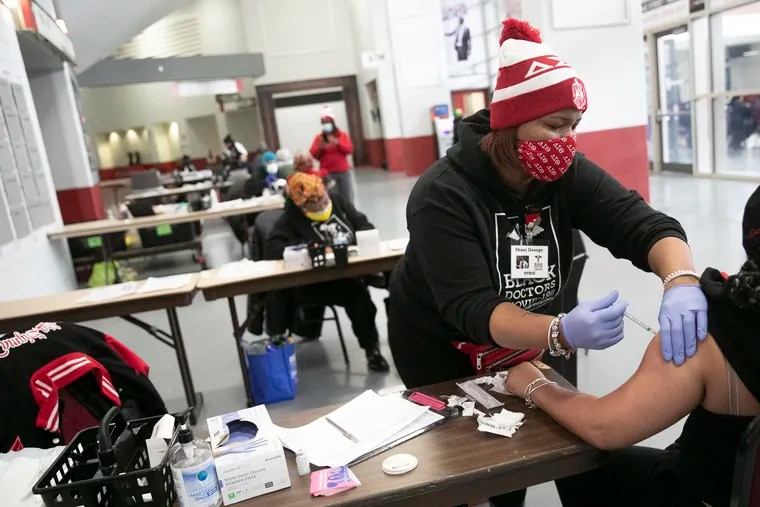 Nurse Shani George administers a COVID-19 vaccine to a patient inside the Liacouras Center. The Black Doctors COVID-19 Consortium has been vaccinating Philadelphia residents.