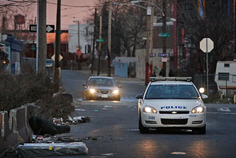 Philadelphia police patrol car secures the crime scene along 100 block of E. Tusculum St. near Front on Thursday morning. The body of a woman was found here Wednesday evening. (Alejandro A. Alvarez/Staff)