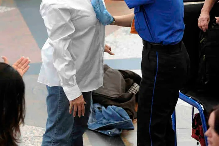 Two travelers undergo searches at Denver International Airport.The pat-downsof breasts and groin areas have drawn objections.