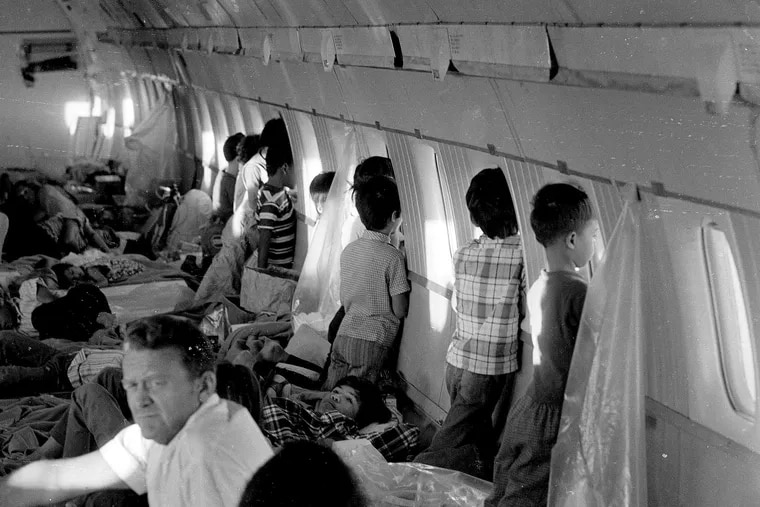"""In this April 1975 file photo, orphans aboard the first """"Operation Babylift"""" flight at the end of the Vietnam War look through the windows of World Airways DC-8 jet as it flies them to the United States."""
