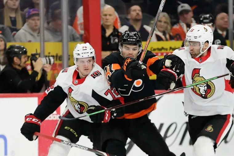 Scott Laughton battles the Ottawa Senators' Thomas Chabot (left) and Colin White (right) on Saturday. The Flyers' forward scored the game-winning goal and contributed an assist and four hits in a 4-3 victory.