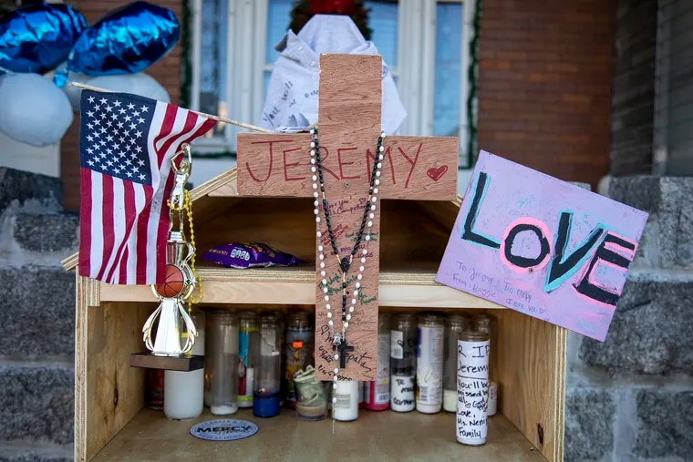 A memorial made by a neighbor was built in front of their home with flowers, candles, messages and photos for the family to remember Jeremy Perez and his father Jesus Perez in North Philadelphia, on Tuesday.