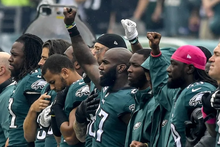 Eagles' Malcolm Jenkins (center) and some teammates raise their right fist during the national anthem before the Arizona game.