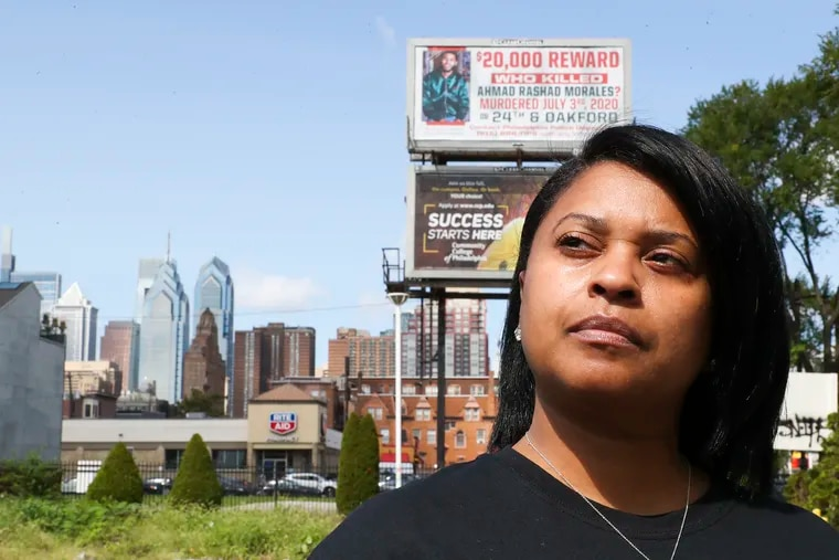 Tamika Morales poses for a portrait in front of the billboard she crowd-sourced for her son, Ahmad Rashad Morales, who was murdered on July 3, 2020, at the corner Broad and Carpenter street in Philadelphia on Friday, Sept. 10, 2021.