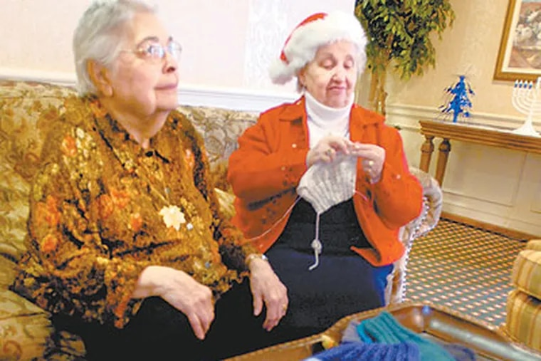 Lorraine Brown (left) and Doris Grossman talk as Doris knits items that will be given to amputees. (Ron Tarver / Staff Photographer)