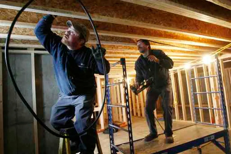 Construction boom? Jeff Rose (left) and Wayne Green of Gillespie Fuels install a heating system in Vermont. Improved weather in November helped new-home construction rebound.