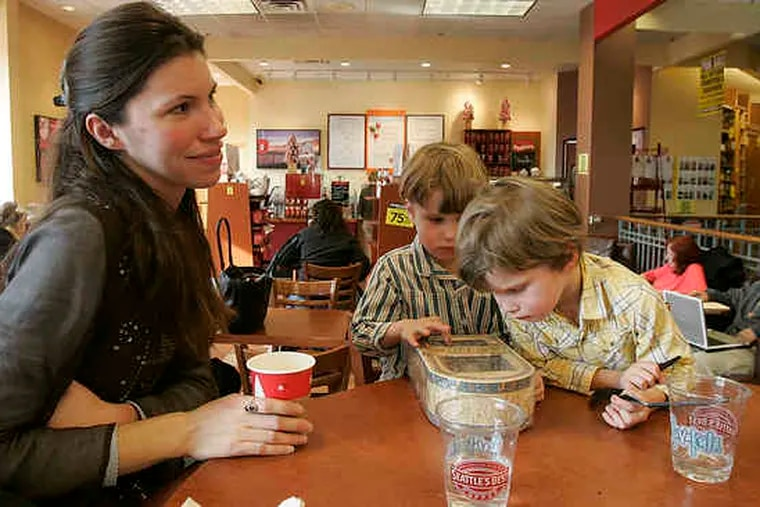 Marie Crosby and her 4-year-old twins, Cullen and Edan, relax in the coffee shop at the Borders store in Chestnut Hill. The longtime fixture at the top of Germantown Avenue attracted lots of bargain hunters on the last day it was open for business.