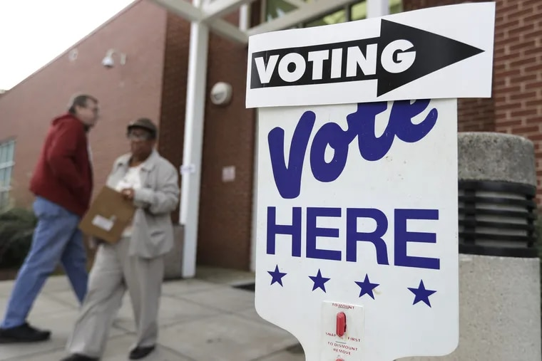 A voter arrives as a worker walks past during early voting at a polling place in Charlotte, N.C.,  in late October.