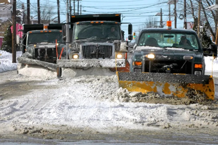 A snow plow train moves along Maple Avenue on the border between Pennsauken and Cherry Hill on Monday after a Christmas weekend snowstorm. (Tom Gralish / Staff Photographer)