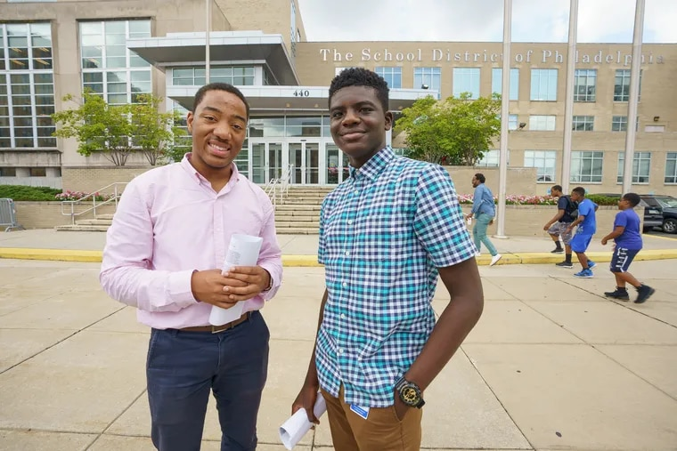 Philadelphia School District students Horace Ryans III, left, and Khalid Abogourin, right, authors of the handbook, shown here holding copies of the handbook for new teachers they co-authored, along with another student.
