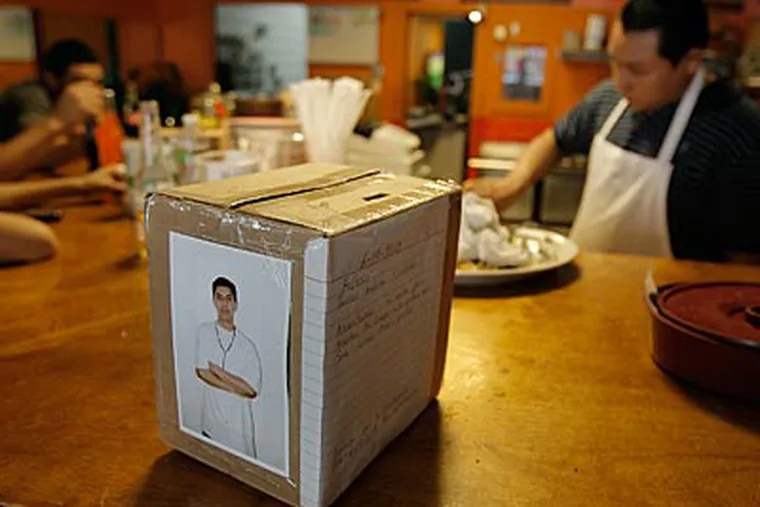 A picture of Javier Medina is pasted on a donation box on the counter of La Toca Loca Restaurant. (Akira Suwa / Staff Photographer)