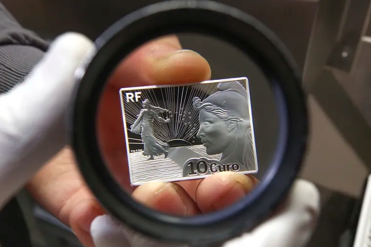 A new strike of a silver coin made in commemoration of the 20th anniversary of the euro currency is seen through a magnifying glass during an event at the National Mint in Paris on Jan. 25. The first euro coins were minted at France's National Mint in 1998. The currency started trading in 1999 and went into circulation in 2002.