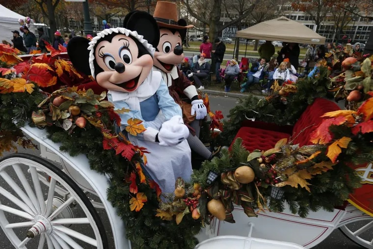 Minnie and Mickey Mouse ride a carriage along the Ben Franklin Parkway during the 2016 Thanksgiving Day parade in Philadelphia.