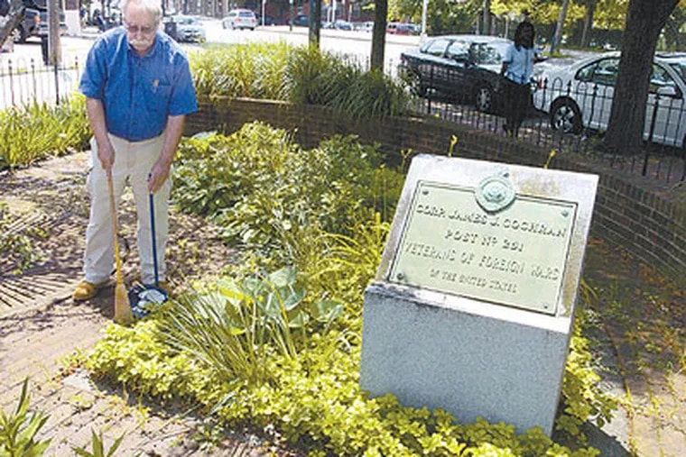 Joel Spivak sweeps trash in a small veterans park at the corner of 37th Street and Lancaster Avenue. (Ron Tarver / Staff Photographer)