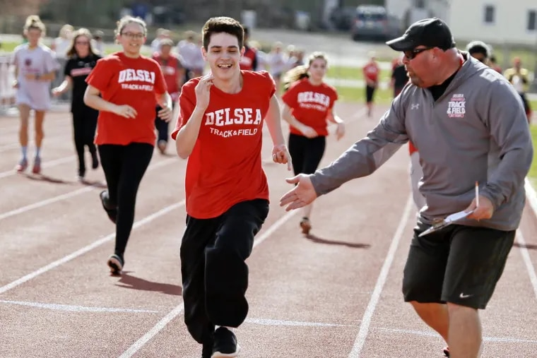 Delsea track and field coach Ronn Flaim encourages Crusaders senior Noah Bekeshka during the Unified Sports track meet.