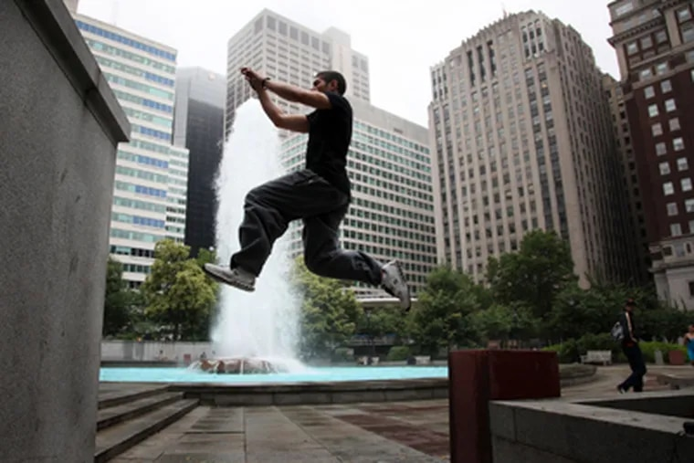 """Gabe Streisfeld leaps between walls at Love Park while demonstrating """"Parkour"""" in Center City. (Laurence Kesterson/Staff Photographer)"""