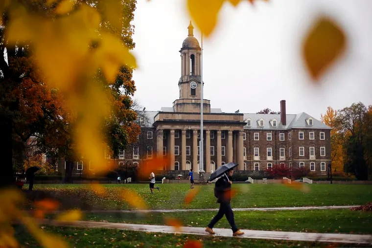 A student walks in the rain past Old Main on the Penn State main campus in State College, Pa., in this October 2015 photo.