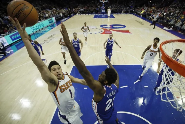 The Suns' Devin Booker goes up for a shot against 76ers center Joel Embiid during the first half Monday night.