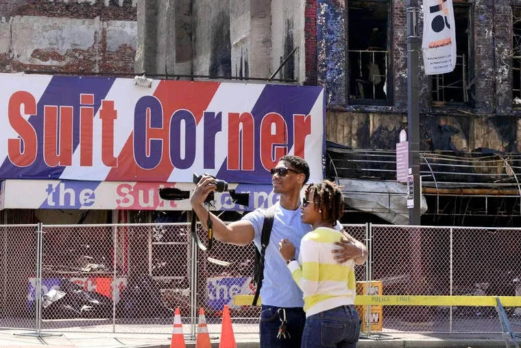 Allen Haynes and DeAnne White, visiting from Queens, N.Y., snap a picture across from the Suit Corner. Fire destroyed the building just weeks after its neighbor, the Shirt Corner, collapsed.