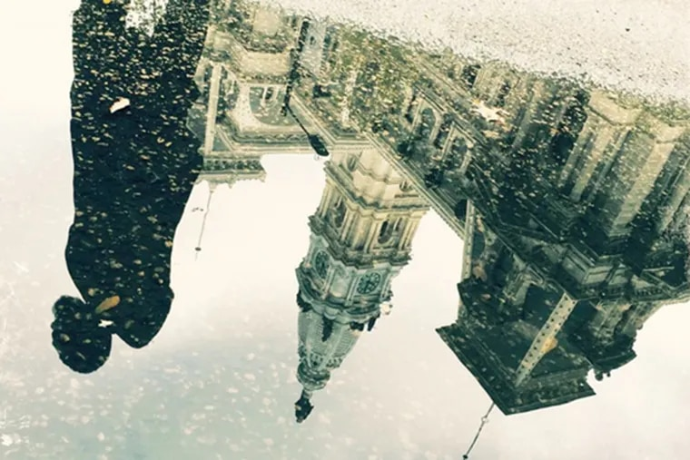 A man's image is reflected in a puddle in front of City Hall in Pennsylvania.