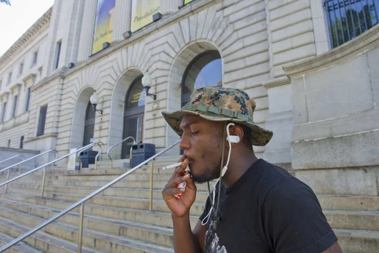 RRXSMOKE12 -- 8/11/16 -- Community College of Philadelphia student Omar Montigue of North Philadelphia has a smoke outside the school's main building along Spring Garden Street.  The college will be instituting a school wide ban on smoking throughout the entire campus.  (Avi Steinhardt/ For the Philadelphia Inquirer)