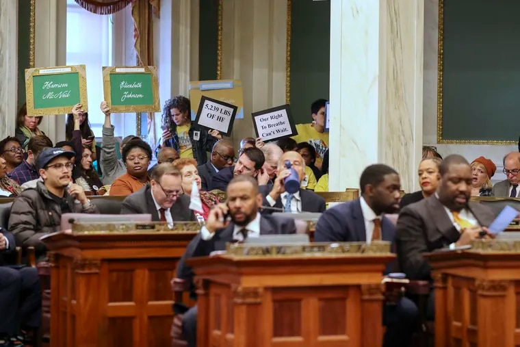 Protesters, many with Philly Thrive, sit in on a City Council hearing regarding the June 21 refinery explosion in South Philadelphia on Thursday, Nov. 21, 2019.