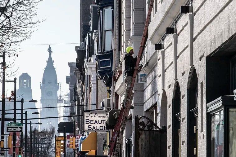 A construction crew works near the intersection of Broad Street and Girard Avenue, with City Hall in the distance. Experts expect more construction to occur on North Broad as a result of the new Opportunity Zones located along the corridor.