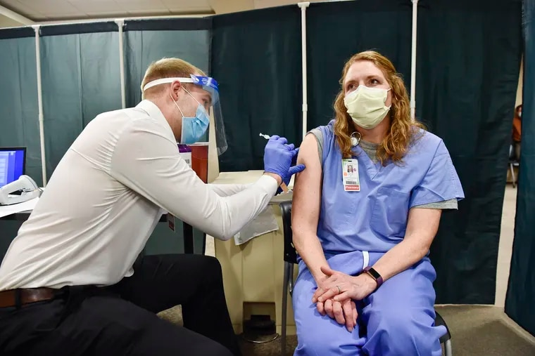 Julie Petre, an ICU pharmacist, receives the Pfizer COVID-19 vaccination at St. Peter's Health in Helena, Mont., in December. Medical providers and Montana residents with compromised immune systems are challenging the only law in the U.S. that prevents state employers from mandating workers get vaccinated.