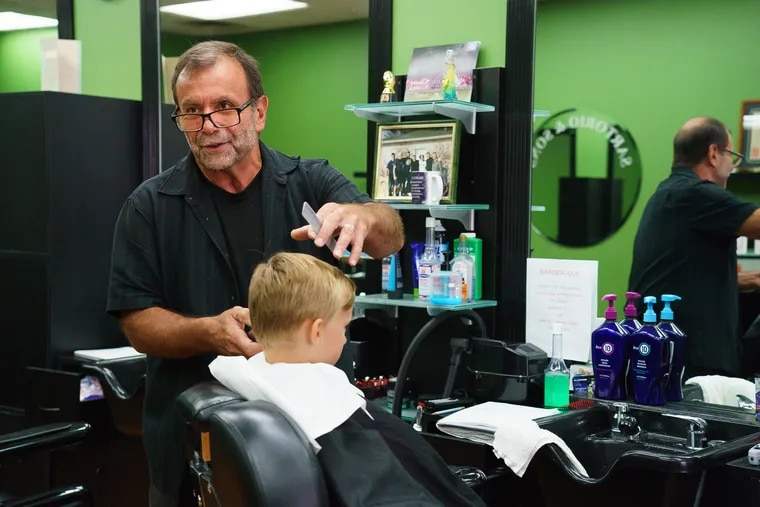 Aldo Sartorio talks with an Inquirer reporter while he cuts hair at Sartorio & Sons Barber Shop, a family business, in Wilkes-Barre, Luzerne County, on Tuesday. Luzerne County was key to President Trump's victory in 2016, and Democrats are working to win back voters like Sartorio. The barber voted for Barack Obama in 2008 and Trump in 2016.