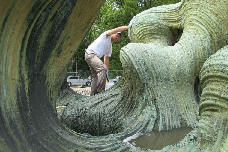 """A conservator cleans Harry Bertoia's 1967 sculpture """"Free Interpretation of Plant Forms"""" at the Woodmere Art Museum in Chestnut Hill, where the sculpture has recently been moved. When the Civic Center was razed in 2000, the fountain was put in storage. It last saw water in 2000."""