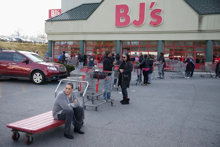 Jacqueline Moss-Holland of Philadelphia, left, sits on a cart as hundreds of shoppers line up to enter BJ's Wholesale Club in Springfield, Pa., before it opened at 9 a.m. on March 14. Customers were stocking up on food and supplies after Gov. Tom Wolf asked non-essential businesses in Delaware County to close due to the coronavirus pandemic, and more businesses will likely close in the coming days.